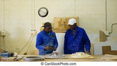 Male workers using digital tablet in workshop 4k