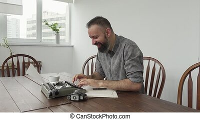 Male writer looking for inspiration and typiing on the...