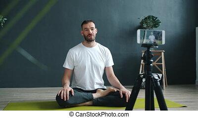 Male yoga teacher recording tutorial using smartphone camera...