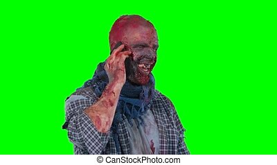 Male zombie using cell phone calling someone, standing on...