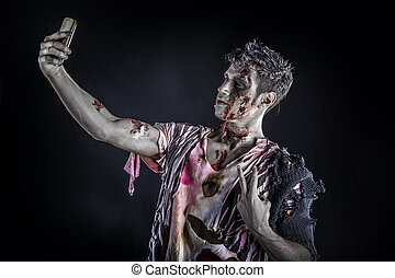 Male zombie using cell phone to take selfie, standing - Male...