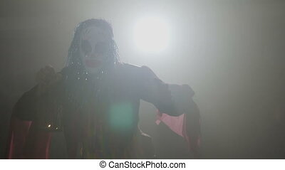 Malefic clown coming out from the dark fog dancing on halloween with a lamp in his hands curiously looking at the camera