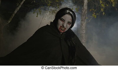 Malefic female zombie vampire getting out from a foggy forest at night in the moonlight to celebrate halloween