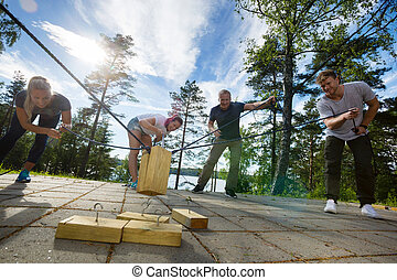 Males And Females Picking Up Wooden Blocks With Ropes -...