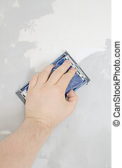Male's hand grinding wall with sandpaper.