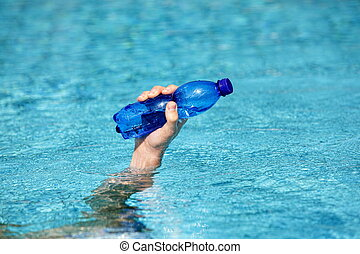 male's hand holding plastic bottle of sweet water on the surface of water