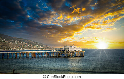 Malibu pier under a cloudy sky at sunset