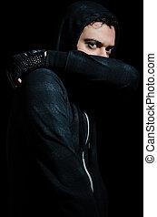 Malicious man sitting in dark
