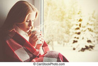 malinconico, triste, ragazza, con, uno, warming, bevanda, guardando fuori, il, finestra, in, il, inverno, foresta
