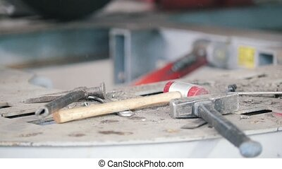 mallet and hammer lie on the work surface against the...