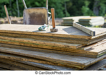 Mallet, protecting gloves and builders level on a pile of wooden planks in an outdoor patio