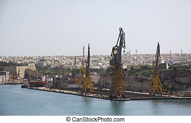 malta drydocks with heavy industial cranes next to harbor