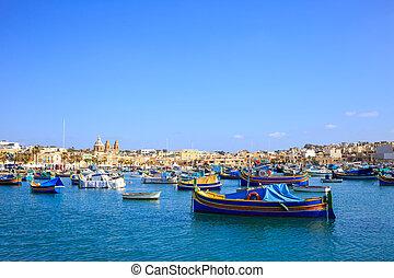 Malta, Marsaxlokk historic port full of boats. Blue sky and village background.