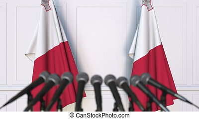 Maltese official press conference. Flags of Malta and...