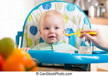 mamá, alimenta, divertido, bebé con, cuchara