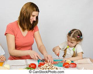 mamá, enseña, hija, a, un, six-year, corte, con, un, cuchillo, productos, para, cocina, en, el, tabla de cocina