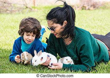 mamá, y, hijo, tenencia, pequeño, conejos, en, jardín