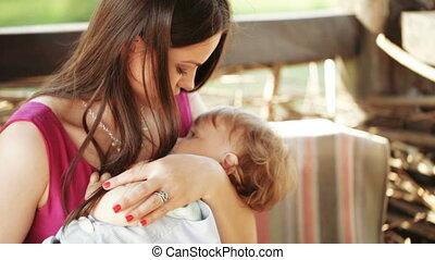 Mama cradles baby on nature