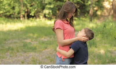 Mama gently hugs her son in the park