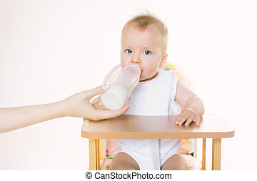 Mama's hand feeds the baby out of the bottle. The child is seated in a chair on a white background