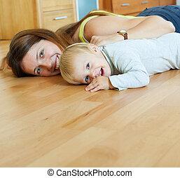mami feliz, y, niño, en, piso de madera