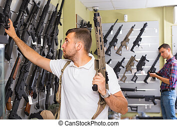 Man 20-30 years old is choosing air-powered gun in army market. High quality photo