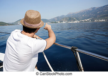 man aboard a boat looking at the sea