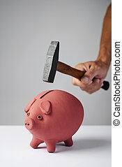 man about to break a piggy bank with a hammer