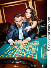 Man accompanied by woman at the casino table