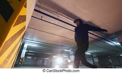 Man acrobat shows tricks somersault at underground parking,...