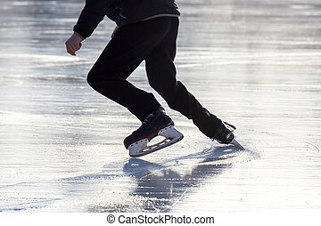man actively skates on an ice rink.