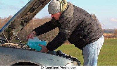 Man adding wash fluid for window