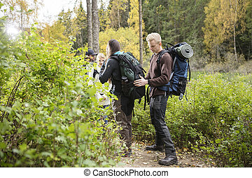 Man Adjusting Backpack Of Friend During Hike In Forest