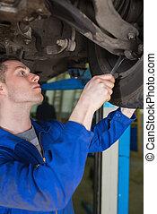 Man adjusting car tire with spanner