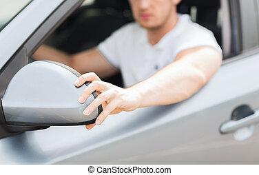 man adjusting rear view mirror - transportation and vehicle...