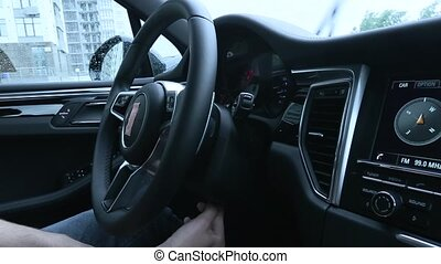 Man adjusts the position of the steering wheel in the car