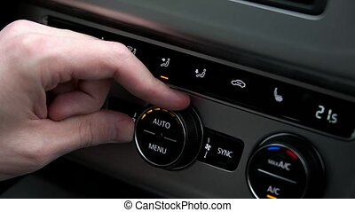 Man adjusts the temperature in the car