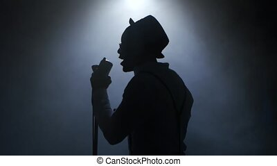 Man african american in half of the turnover in the smoke and white light approaching the retro microphone singing in a recording studio. Black background. Silhouette. Close up