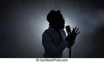 Man african american singer in the smoke and white light...