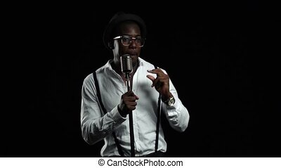 Man african american singer sings into a microphone and dance. Black background. Slow motion
