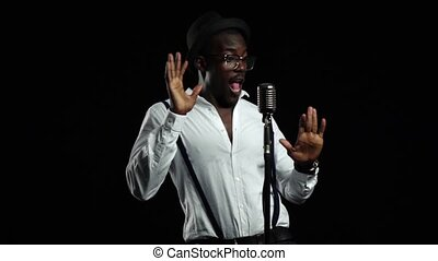 Man african american singer sings into a microphone and dancing. Black background. Slow motion. Close up