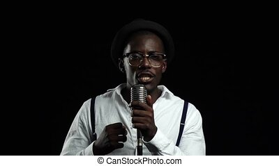 Man african american standing at the microphone professionally singing in a recording studio. Black background. Slow motion. Close up