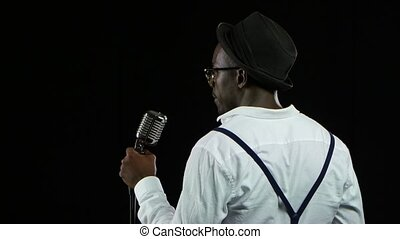 Man african american the view from the back standing at the microphone professionally singing in a recording studio. Black background. Close up