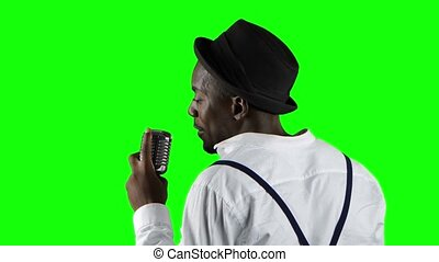 Man african american the view from the back standing at the microphone professionally singing in a recording studio. Green screen. Close up