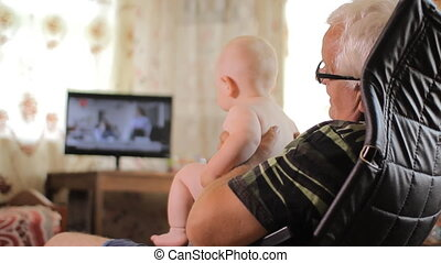 Man aged holding baby in her arms and watching TV. Baby less than a year. Home interior