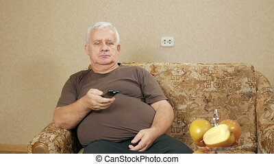 Man aged switches remote control TV channels on the couch at home. He relaxes after a hard day. holiday home concept