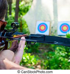 Man aiming crossbow at target