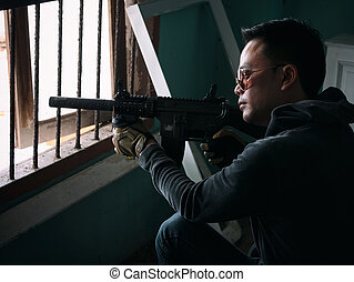 Man aiming the gun to an invisible target with a sniper , selective focus to gun