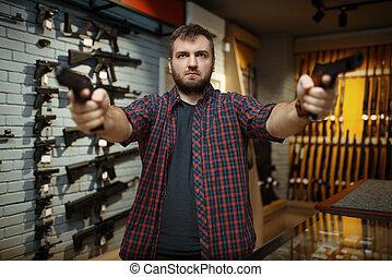 Man aims with two handguns in gun shop