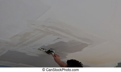 Closeup of a man aligning a wall with spatula and plastering gypsum cardboard ceiling